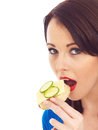 Young Woman Eating Toasted Crumpet with Cheese and Cucumber Royalty Free Stock Photo