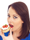 Young Woman Eating Toasted Crumpet with Cream Cheese and Tomato Royalty Free Stock Photo