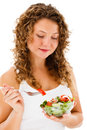 Young woman eating vegetable salad isolated white background Stock Images