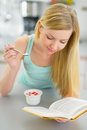 Young woman eating yogurt and reading book in kitchen Stock Image