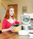 Young woman with electric slo cooker at home Stock Photos