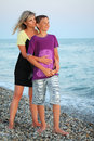 Young woman embraces smiling boy on beach Royalty Free Stock Image
