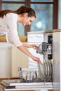 Young woman empty out the full dishwasher Royalty Free Stock Photo