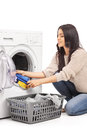 Young woman emptying a washing machine vertical shot of isolated on white background Stock Image