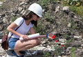 Young woman engineer environmental with white helmet examining red poppy flower Royalty Free Stock Photography