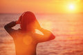 Young woman enjoying beautiful sunset over the sea in headphones listening music and rear view image with sunlight effect Stock Photo