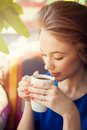 Young woman enjoying a cup of coffee in soft focus portrait Royalty Free Stock Photo