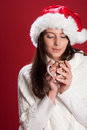 Young woman enjoying a cup of hot chocolate beautiful brunette caucasian wearing white sweater and santa s hat on red background Stock Images