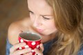 Young woman enjoying cup of tea close up portrait a Stock Image