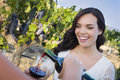 Young woman enjoying glass of wine in vineyard with friends pretty mixed race adult a the Royalty Free Stock Photos