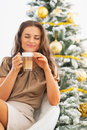 Young woman enjoying latte macchiato in front of christmas tree portrait happy Stock Photos