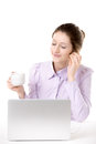 Young woman enjoying music with cup of coffee in front of comput resting computer earphones closed eyes relaxing Royalty Free Stock Photo