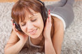 Young woman enjoying music in headphones beautiful lying on the floor at home sensual female relaxing Stock Photos