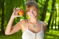 Young woman enjoying nature showing an apple as health symbol Stock Photos