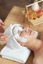 A young woman enjoying spa mask women at beauty salon indoors Stock Photo