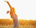 Young woman enjoying sunlight with raised arms in straw field Royalty Free Stock Photo