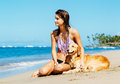 Young woman enjoying sunny day at the beach with her dog attractive golden retriever Stock Image