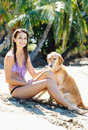 Young woman enjoying sunny day at the beach with her dog attractive golden retriever Royalty Free Stock Photo