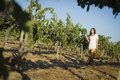 Young woman enjoying a walk and wine in vineyard mixed race glass of the Royalty Free Stock Image