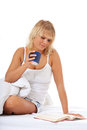 Young woman enjoys cup of coffee in bed attractive first all on white background Royalty Free Stock Photos