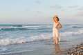 Young woman enjoys a lonesome walk on the beach at dusk barefoot in long white partially wet dress in water sandy in late summer Stock Photography