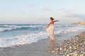 Young woman enjoys a lonesome walk on the beach at dusk barefoot in long white partially wet dress in water sandy in late summer Royalty Free Stock Photos