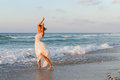 Young woman enjoys a lonesome walk on the beach at dusk barefoot in long white partially wet dress in water sandy in late summer Stock Photo