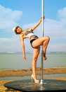Young woman exercise pole dance slim in hat outdoors Stock Image