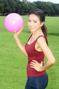 Young woman exercised with pink ball in the garden Royalty Free Stock Photography