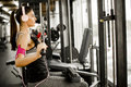 Young woman exercises on an exercise machine at the gym listenin Royalty Free Stock Photo