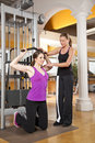 Young woman exercising in gym with trainer Stock Image