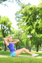 Young woman exercising on a mat in a park blond Royalty Free Stock Images