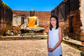 Young woman is exploring the ancient ruins of a buddhist temple