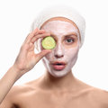 Young woman with a face pack cucumber mask girl cosmetic cream on cheek skin care concept closeup portrait isolated on Stock Photos