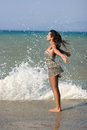 Young woman facing the waves splashing on a concrete pier Stock Photos