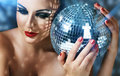 Young woman with fashionable makeup close up face of make up and disco ball in hands Royalty Free Stock Photo