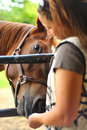 Young woman feeding horse Royalty Free Stock Images