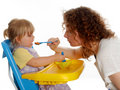 Young woman feeding little girl Stock Photos