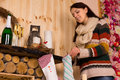 Young woman filling christmas stockings in a rustic wooden cabin hanging on the hearth with a bottle and glasses of champagne on Stock Images