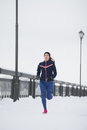 Young woman fitness model running at snow winter park, pink sneakers Royalty Free Stock Photo