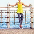 Young woman in fitness outfit looking aside at embankment Royalty Free Stock Photo