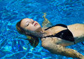 Young woman floats in a swimming pool Royalty Free Stock Photo