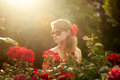 Young woman in flower garden smelling red roses #1 Stock Photo