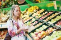 Young woman at food shopping in supermarket choosing bio fruit apple vegetable during Royalty Free Stock Photography