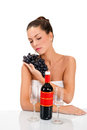 Young woman and fresh grapes a holding on the table two glasses a bottle of wine Royalty Free Stock Images