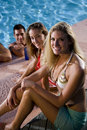 Young woman with friends by swimming pool Stock Photos