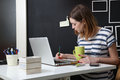 Young woman in front of laptop writing a note Royalty Free Stock Photography