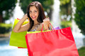 Young woman with full of shopping bags female beauty huge in front fountains along a mall Royalty Free Stock Photo