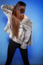 Young woman in fur long hair blue background fashionable coat back view Stock Photo
