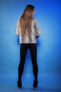 Young woman in fur long hair blue background full length fashionable coat back view Stock Photo